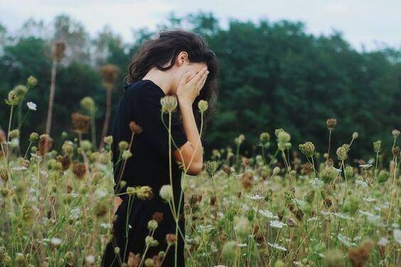 Frau steht auf einer Blumenwiese und hält sich ihre Hände vors Gesicht