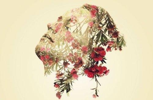 Ein Gesicht schwebt in der Luft, geformt aus pinken Blüten und Blättern.