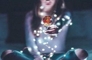 Glück finden - Lichter vor einer Frau im Lotussitz