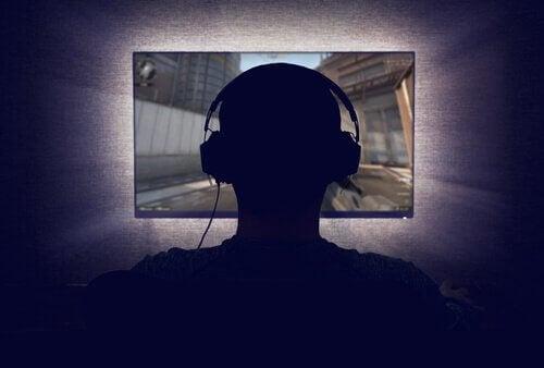 Hikikomori - Jugendlicher mit Kopfhörern schaut auf Bildschirm