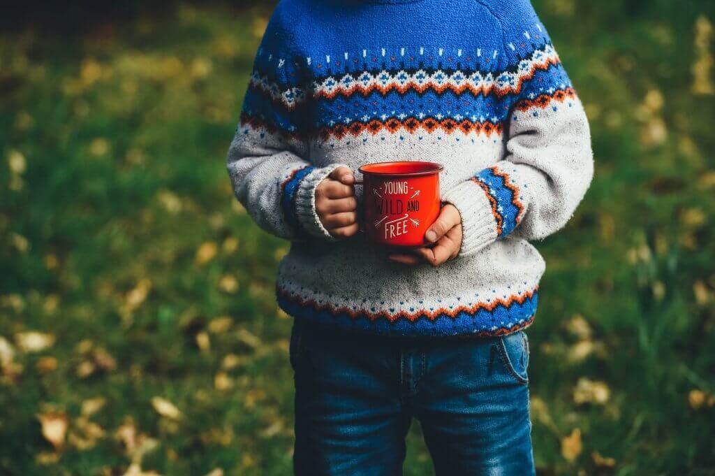 Ein Junge hält eine Tasse.