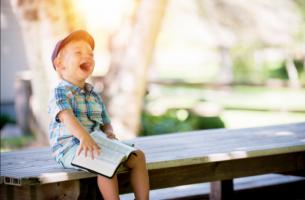Kinder mit Lernschwierigkeiten - lachenderJunge mit Buch