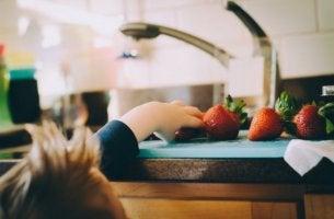 Übergewicht bei Kindern - Ein Junge nimmt sich eine Erdbeere.