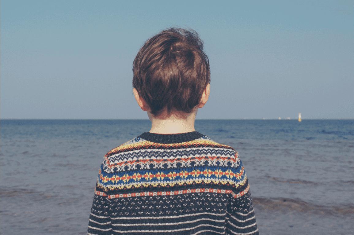 Kleiner Junge blickt aufs weite Meer hinaus