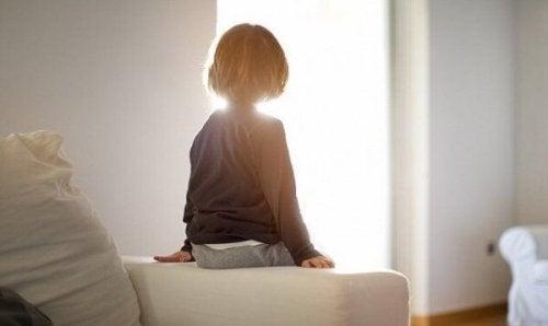 Junge sitzt auf einer Couch und schaut zum Fenster hinaus