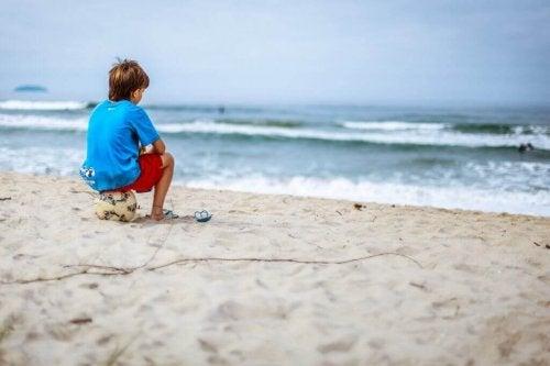 Junge sitzt auf einem Ball am Strand