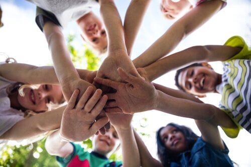 Kinder legen ihre Hände aufeinander