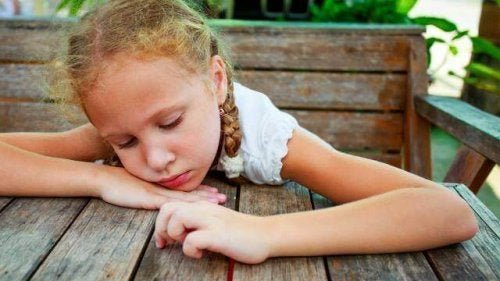 Trauriges Mädchen an einem Tisch