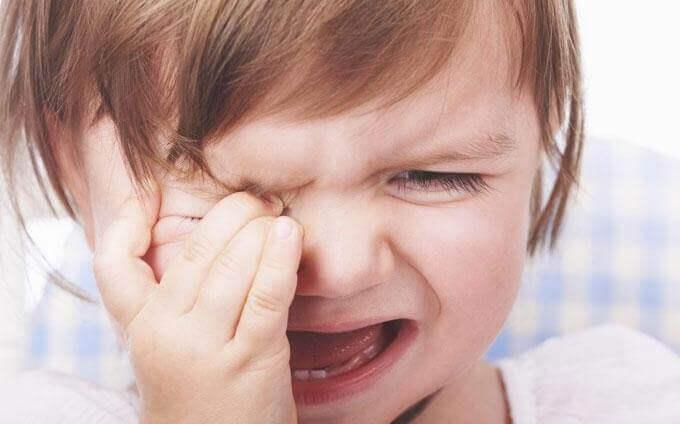 Kleines Mädchen kneift sich weinend ins Auge