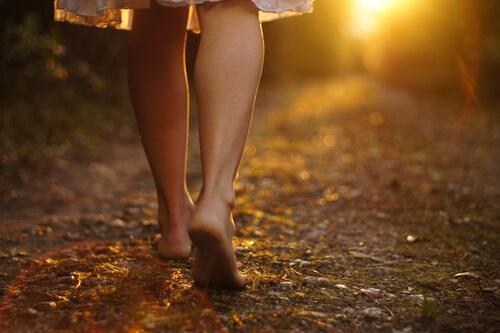 Frau läuf auf einem Weg voller Blätter bei Sonnenuntergang