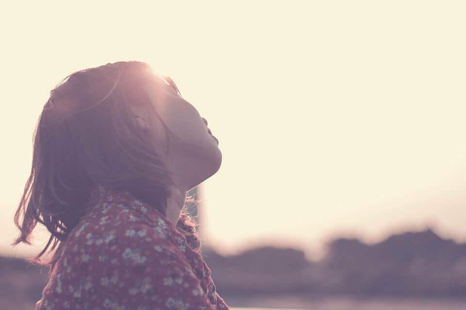 Mädchen sitzt allein in der Sonne