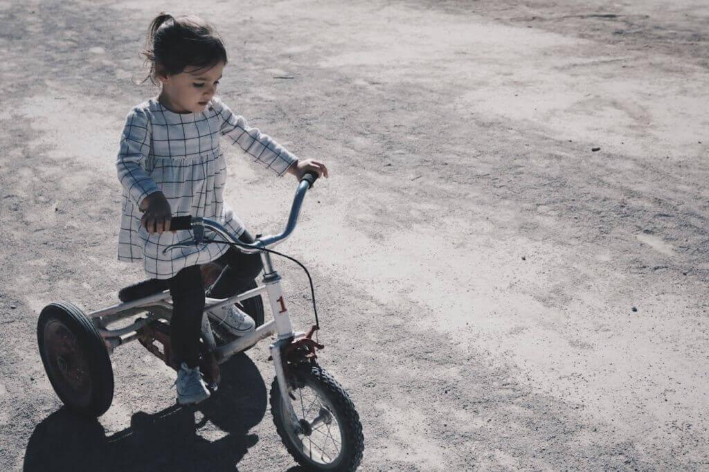 Das Beste gegen Übergewicht bei Kindern ist Bewegung. Ein Mädchen fährt Dreirad.