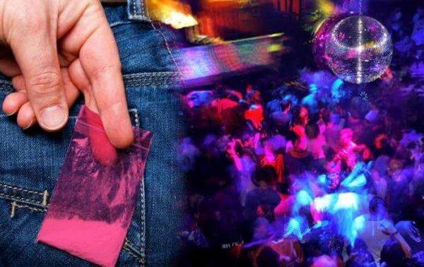 In einer Diskothek hält ein Mann, der in Jeans gekleidet ist, ein Tütchen mit einer Droge an die hintere Gesäßtasche.