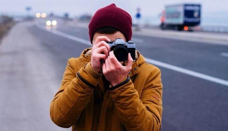 Mann mit Kamera macht ein Foto