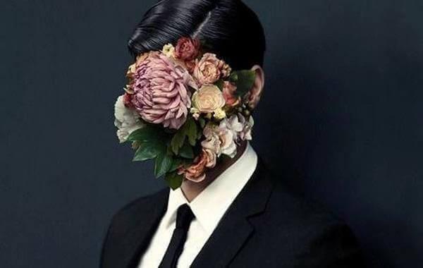 Mann im Anzug mit pomadigem Haar trägt statt eines Gesichtes ein Blumenarrangement.