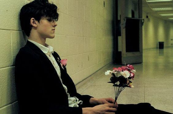 Trauriger Mann sitzt mit Blumentrauß auf dem Boden