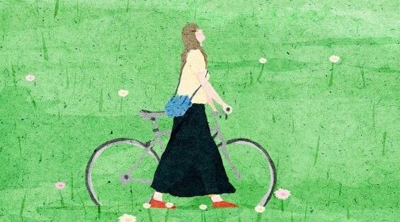 Frau schiebt ihr Fahrrad über eine grüne Wiese