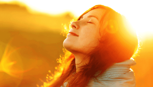 Frau schaut mit geschlossenen Augen hoch in Richtung Sonne