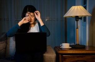 Berufliches von Privatem trennen - Müde Frau arbeitet in ihrem Zuhause.