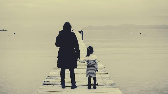 Mutter steht mit ihrer Tochter auf einem Steg