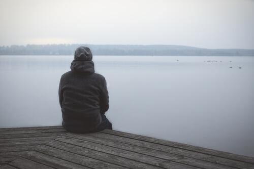 Nachdenklicher Mann schaut auf einen See hinaus