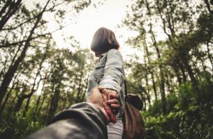 Gemeinsam Resilienz steigern - Paar geht Hand in Hand durch den Wald