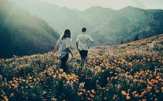 Paar geht auf Blumenwiese in den Bergen