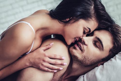 Frau umarmt und küsst ihren Partner von hinten