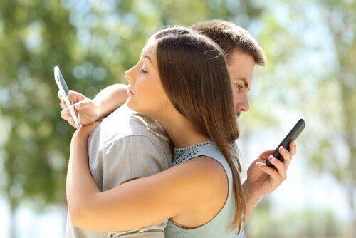 Partner umarmen sich, während sie auf ihre Telefone schauen