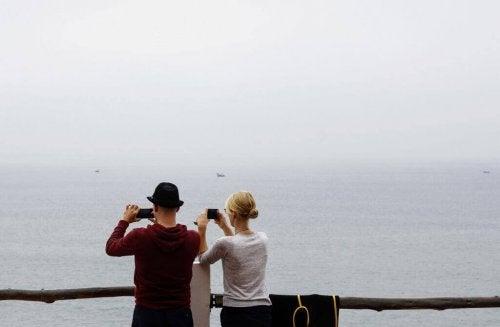 Partner machen mit ihren Handys Fotos