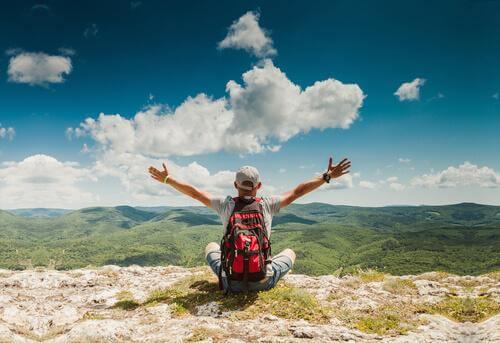 Reiselustiger Mann sitzt auf einem Berg