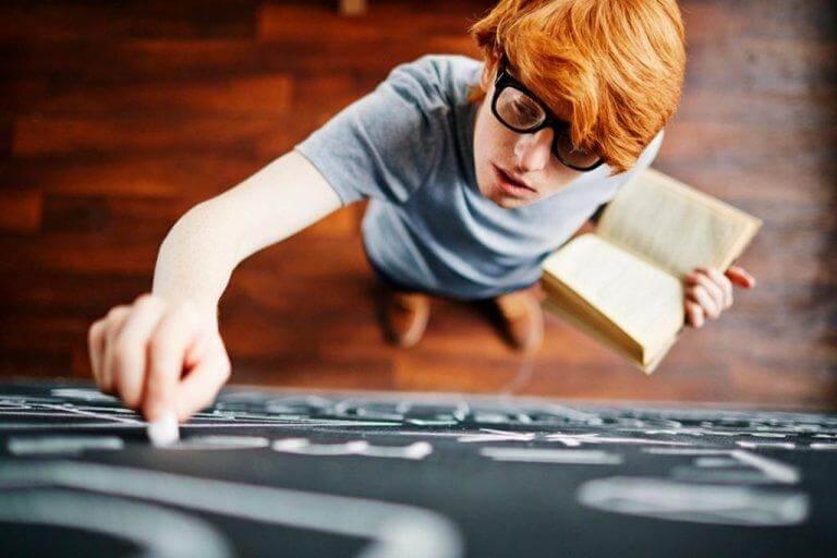 Schlauer junger Mann schreibt etwas an eine Tafel