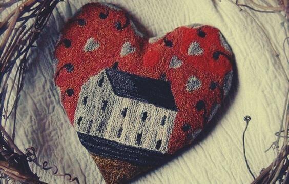 Ein rotes Herz aus Stoff mit einem Haus darauf