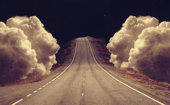 Straße umgeben von großen Wolken