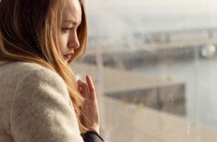 Illusion der Kontrolle - Traurige Frau schaut aus dem Fenster.