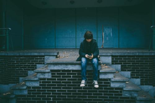 Trauriges Kind sitzt auf einer Treppe und schaut auf sein Telefon