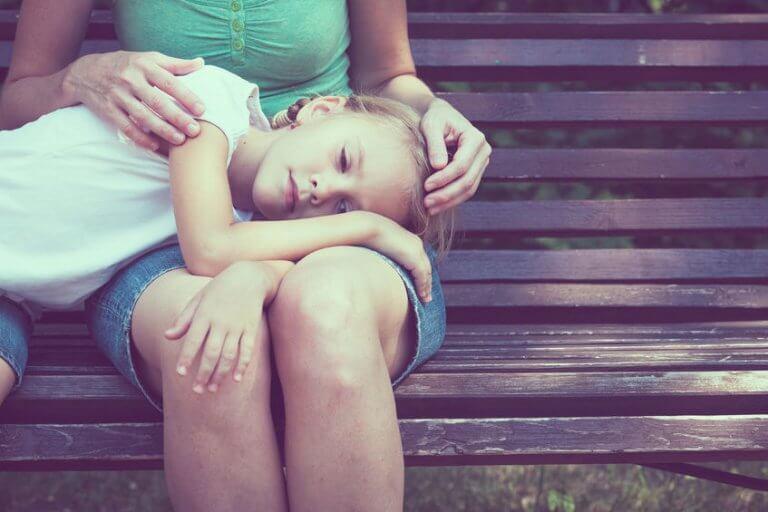 Trauriges Mädchen, das von der Mutter getröstet wird, während es den Kopf auf deren Schoß gelegt hat