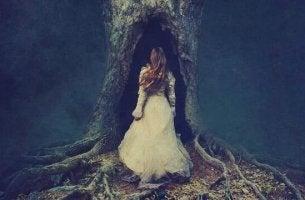 Ungelöstes emotionales Leid - Frau tritt in einen Baumstamm ein