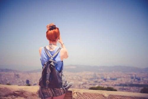 Frau im Urlaub schaut mit dem Fernglas auf eine Stadt
