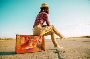 Wanderlust-Gen - Frau sitzt an einer Straße auf ihrem Koffer