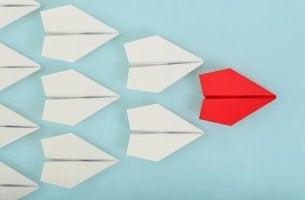 Was macht einen Anführer aus? - roter Papierflieger vor weißen Papierfliegern