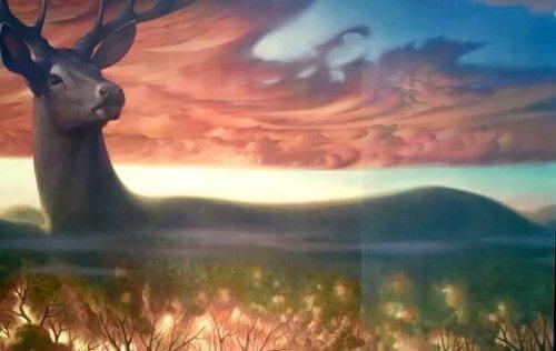 Hirsch in magischer Landschaft bei Sonnenaufgang.