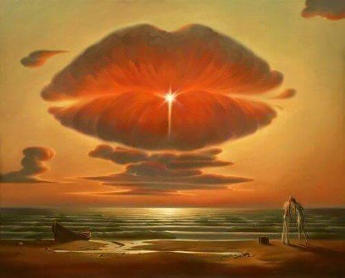 Paar küsst sich am Strand vor großer Wolke in Form eines Kussmundes.