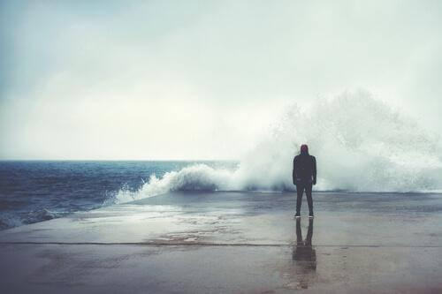 Mann schaut auf eine große, brechende Welle