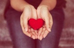 gewaltfreie Kommunikation - Die Hände einer Frau öffen sich zu einer Schale. Darin liegt ein rotes, gehäkeltes Herz.