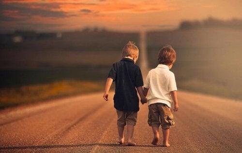 Zwei Jungen laufen gemeinsam auf einer Straße.