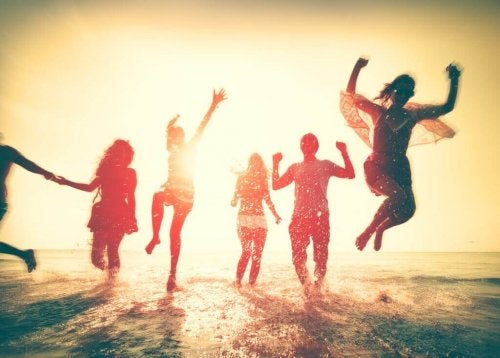 Freunde sind am Strand und springen in die Luft.