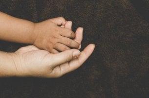 Bindungsverhalten von adoptierten Kindern - Adoptiertes Kind hält die Hand seiner Mutter