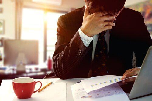 Ein Mann auf der Arbeit hält erschöpft eine Hand vor sein Gesicht.