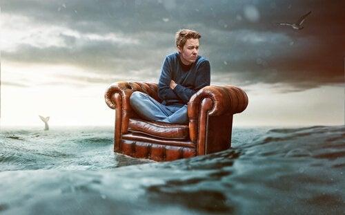 Helfen, aber nicht Eingreifen: Mann, der alleine auf einem Sessel durch das Meer treibt.